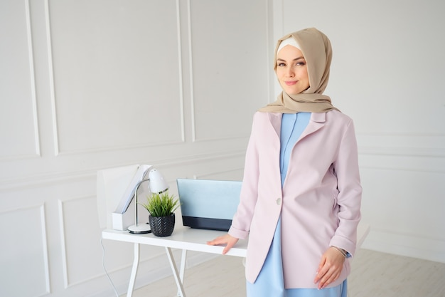 Donna musulmana in hijab beige e vestiti tradizionali in piedi vicino al posto di lavoro