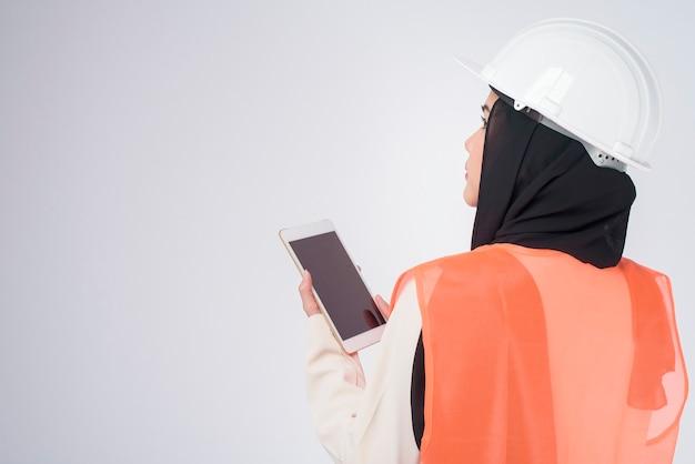 Una donna musulmana ingegnere che indossa un casco protettivo su sfondo bianco studio