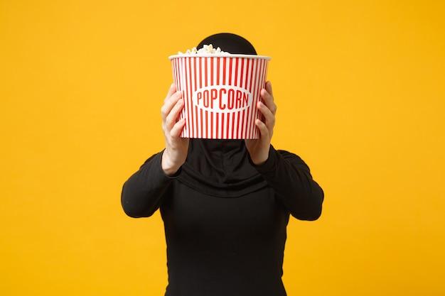 Donna musulmana in hijab vestiti neri occhiali 3d imax guarda film film tenere popcorn, nascondendo il viso pop corn isolato sul ritratto muro giallo. concetto di stile di vita della gente.
