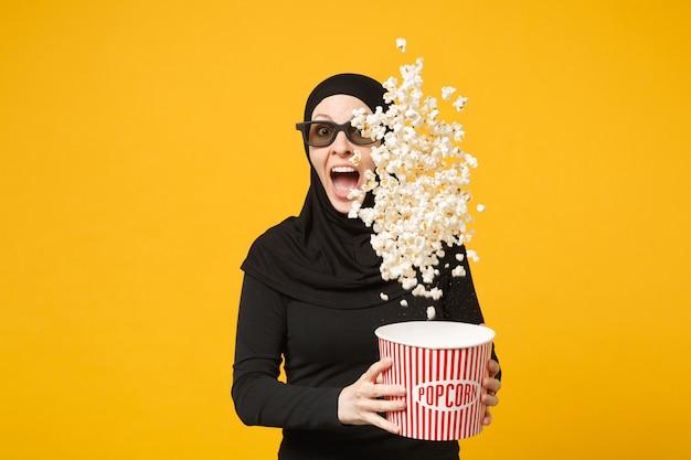 Donna musulmana in hijab vestiti neri occhiali 3d imax guarda film film tenere popcorn, spuntando pop corn isolato su muro giallo ritratto. concetto di stile di vita della gente. .