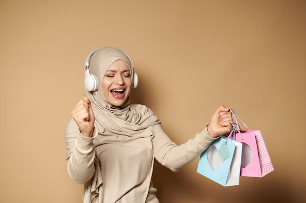 Donna musulmana in hijab con le cuffie che tengono i sacchetti di carta colorati nelle sue mani godendo delle prossime festività religiose. eid mubarak ha detto.