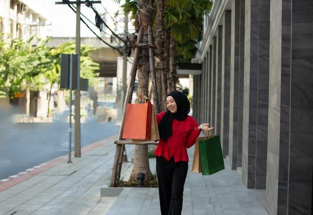Donna musulmana che tiene la borsa della spesa