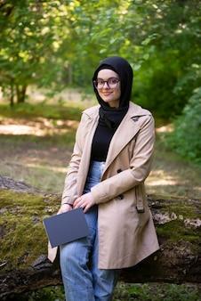 Donna musulmana che legge un libro nel parco durante il suo tempo libero
