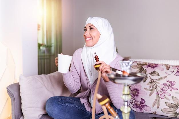 Donna musulmana che fuma shisha a casa e che beve caffè o tè. ragazza araba che fuma narghilè