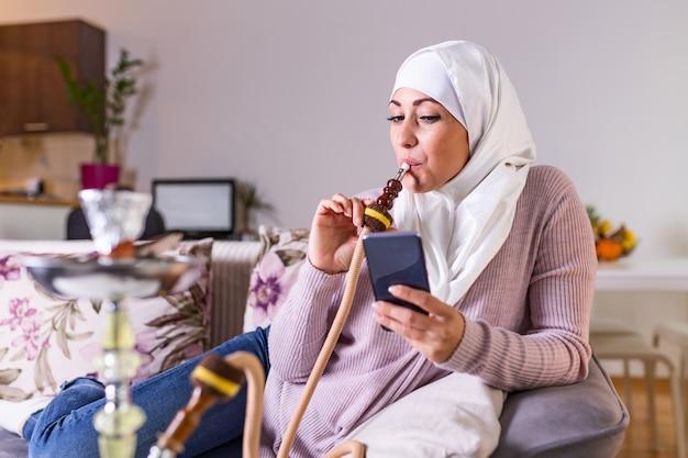 Donna musulmana che fuma shisha a casa e che manda un sms con i suoi amici. ragazza araba che fuma narghilè