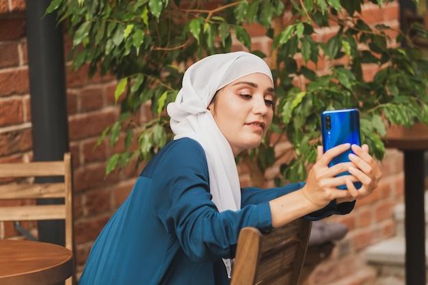 Donna musulmana che si fa selfie felice e bella ragazza con sciarpa si fa una foto usando lo smartphone