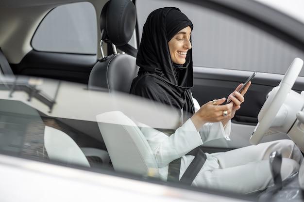 Una donna musulmana parla al telefono mentre guida un'auto