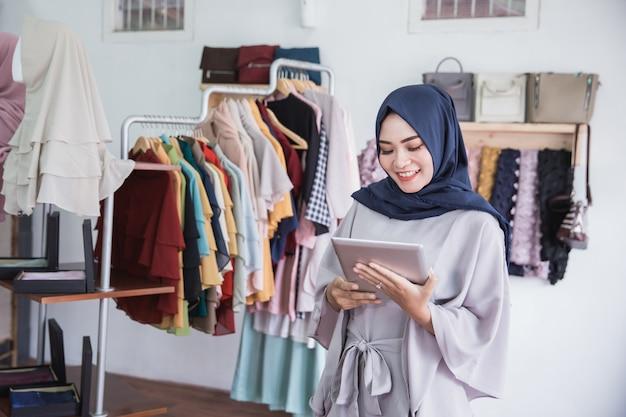 Donna musulmana che utilizza compressa digitale nel negozio di vestiti
