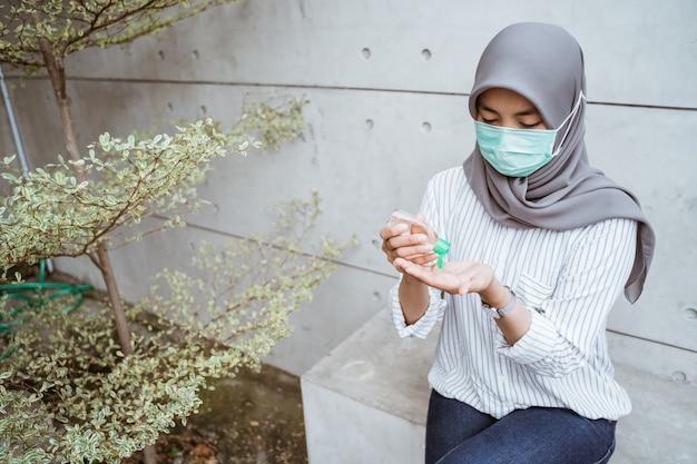 Donna musulmana con gel disinfettante per le mani