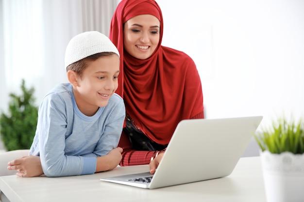 Donna musulmana che usa il laptop con suo figlio a casa
