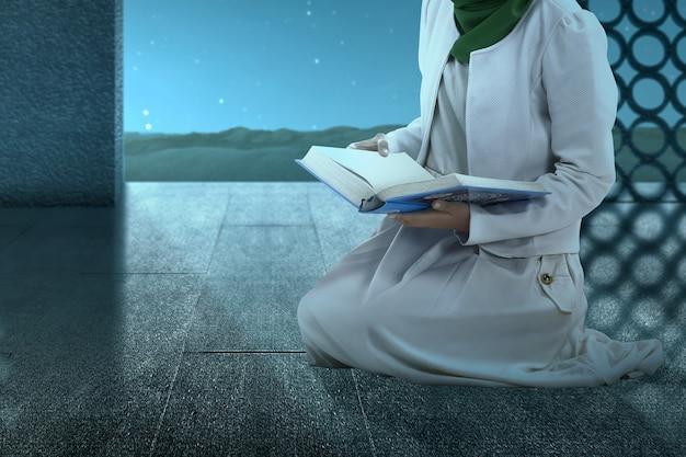 Donna musulmana in un velo seduto e leggendo il corano sulla moschea