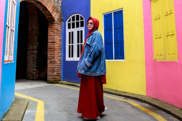 Donna musulmana che indossa un velo rosso e occhiali da sole in posa sul sentiero con una casa colorata e un tunnel di mattoni sullo sfondo