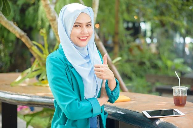 La donna musulmana con l'hijab sta lavorando con il tablet in una caffetteria