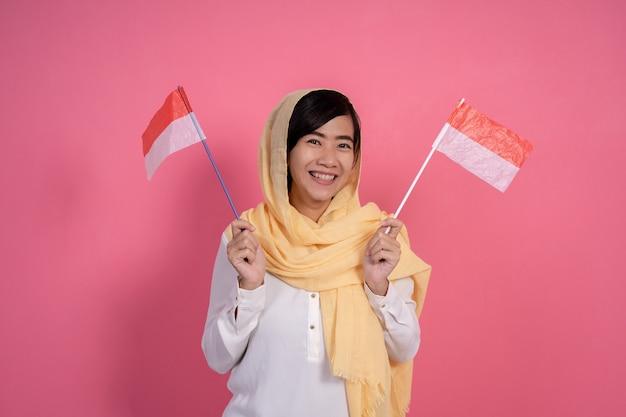 Donna musulmana con la bandiera nazionale dell'indonesia