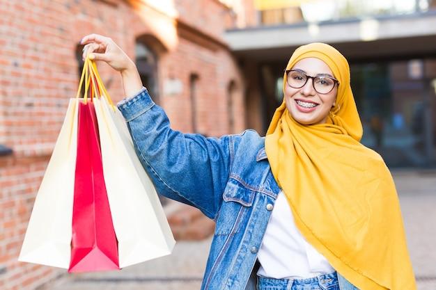 Donna musulmana con borse della spesa