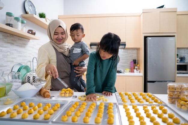 Donna musulmana con due figli che cucinano insieme in cucina facendo uno spuntino