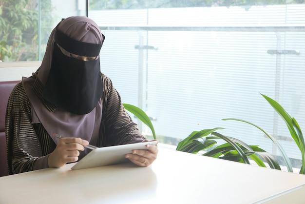 Donne musulmane con sciarpa per la testa utilizzando tavoletta digitale al coperto.