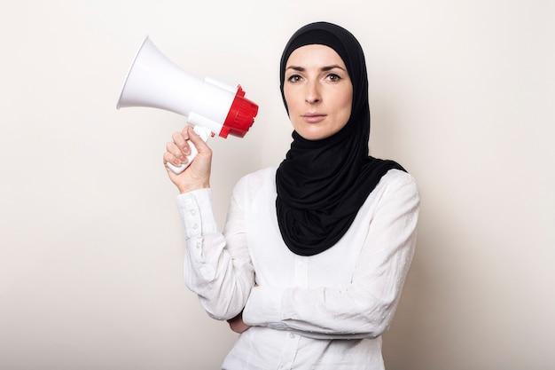La giovane donna musulmana in hijab tiene un megafono nelle sue mani