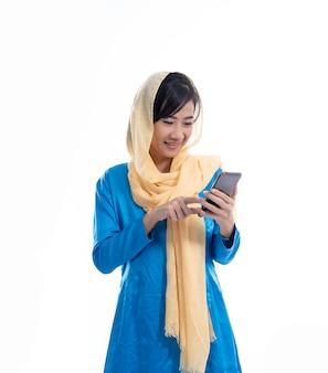 Giovane donna musulmana che per mezzo del telefono cellulare
