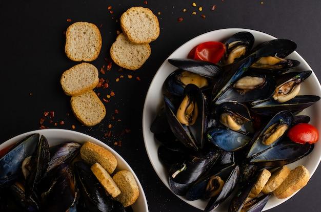 Zuppa di cozze al vapore nel vino con pomodori, peperoncini e pane croccante su sfondo nero. pesce italiano. vista piana, vista dall'alto, copia spazio