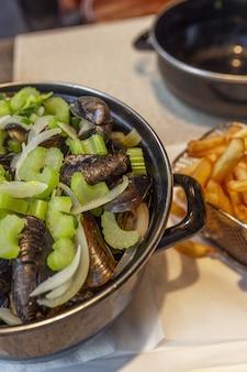 Cozze in una casseruola e patatine fritte su un tavolo in un caffè. spuntino belga tradizionale.