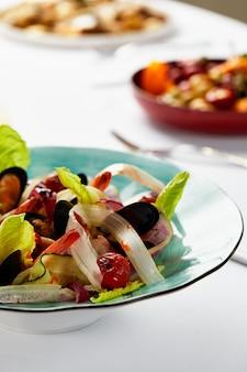 Vongoli di cozze in un piatto con lattuga, cozze cotte in salsa al vino bianco, frutti di mare serviti dallo chef, su sfondo chiaro, primo piano.