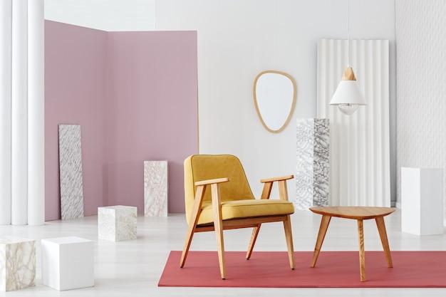 Poltrona di senape in piedi accanto a un tavolo di legno all'interno di una stanza luminosa con colonne di marmo e tappeto rosso