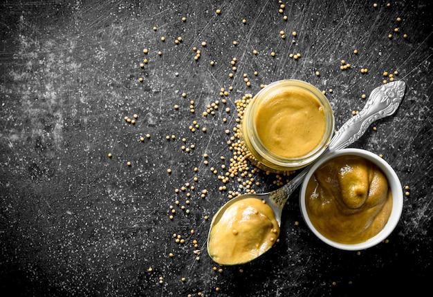 Senape in un barattolo di vetro, ciotola di cucchiaio sul tavolo rustico scuro
