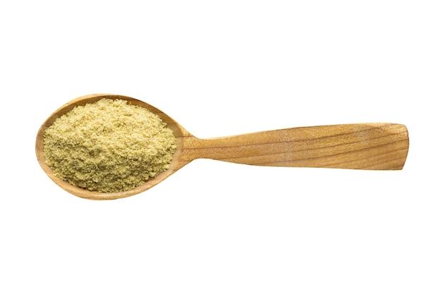 Senape in polvere da aggiungere al cibo. spezia in cucchiaio di legno isolato su bianco. condimento del pasto delizioso.