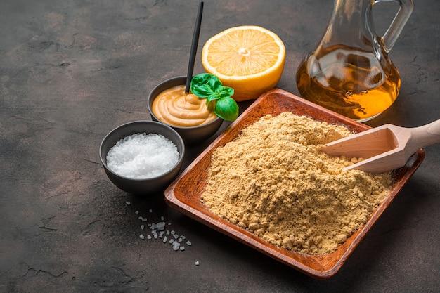 Senape in polvere e ingredienti su uno sfondo marrone con spazio per copiare. il concetto di sfondi culinari.