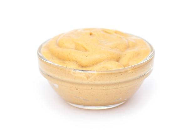 Salsa di senape in una piccola ciotola di vetro, isolata in bianco. salsa di senape come condimento