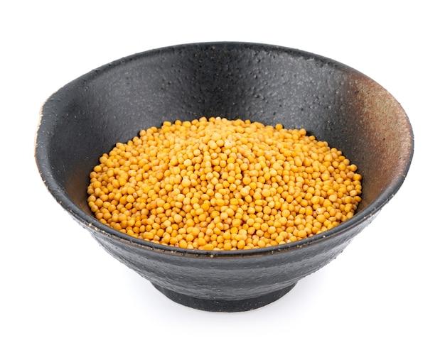 Semi di senape in una ciotola isolata su bianco