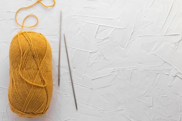 Gomitolo di lana senape e paio di ferri da maglia in metallo. fili arancioni per maglieria.