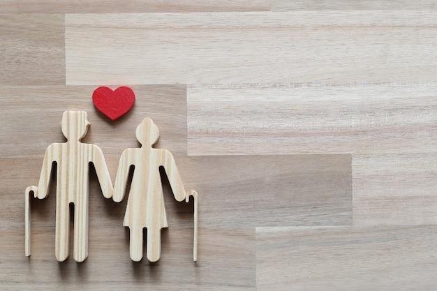 Fondo comune, coppia senior di amore e forma di cuore su fondo di legno