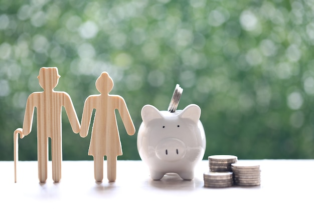 Fondo comune, amore coppia senior e salvadanaio con una pila di monete soldi su sfondo verde naturale