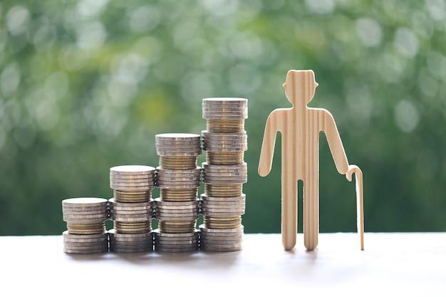 Fondo comune, uomo anziano e pila di monete soldi su sfondo verde naturale, risparmiare denaro per prepararsi in futuro e concetto di pensionamento pensione