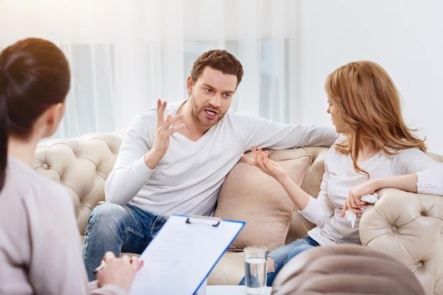 Incomprensione reciproca. uomo bello emotivo arrabbiato alzando la mano e dicendo qualcosa a sua moglie mentre non è d'accordo con lei