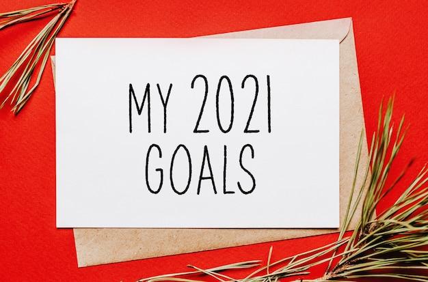 I miei obiettivi 2021 nota di natale con ramo di abete su sfondo rosso isolato. anno nuovo concetto