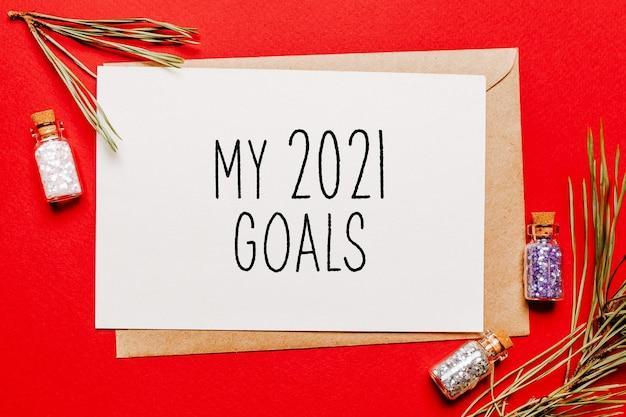 I miei obiettivi 2021 nota di natale con regalo, ramo di abete e giocattolo su sfondo rosso isolato. anno nuovo concetto