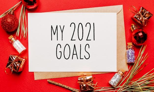 I miei obiettivi 2021 nota di natale con regalo, ramo di abete e giocattolo sul muro rosso isolato. anno nuovo concetto