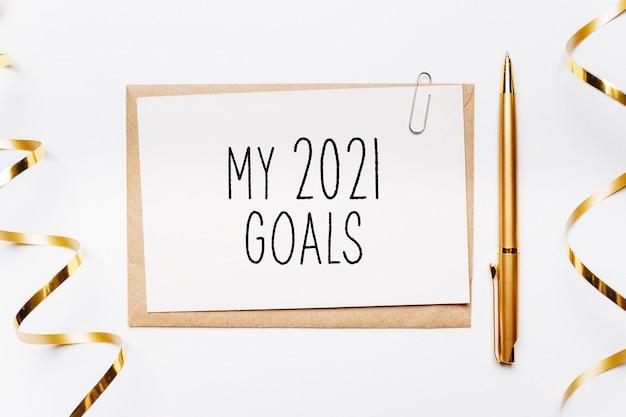 I miei obiettivi per il 2021 si annotano con busta, penna, regali e nastro dorato su sfondo bianco. buon natale e anno nuovo concetto