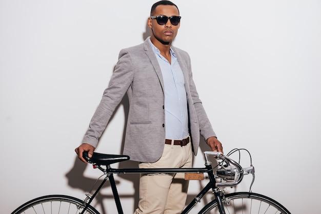 La mia bici è il mio stile di vita. fiducioso giovane africano in occhiali da sole