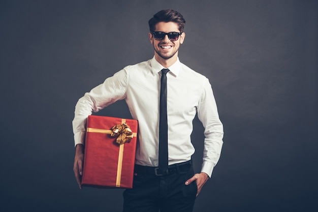 Le mie congratulazioni! allegro bel giovane ben vestito con occhiali da sole che tiene in mano una scatola regalo e guarda la telecamera con un sorriso mentre si trova su uno sfondo grigio