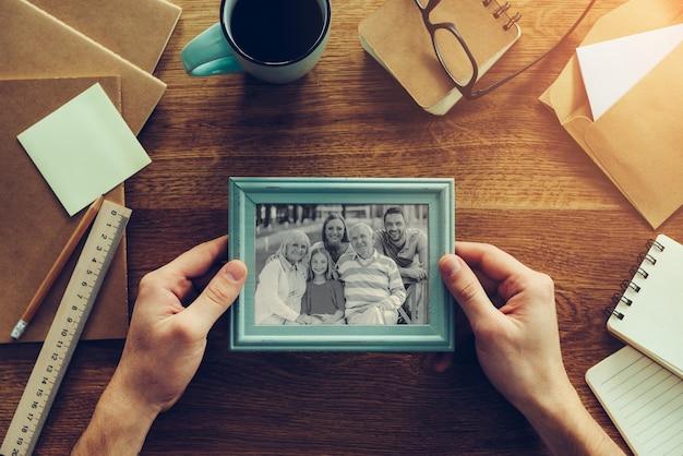 La mia famiglia è la mia ispirazione. vista ravvicinata dall'alto dell'uomo che tiene in mano la fotografia della sua famiglia su una scrivania di legno con diverse cose della cancelleria che giacciono intorno