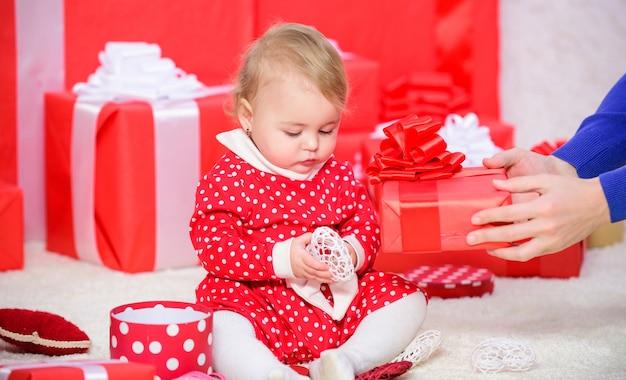 Il mio primo natale. condividere la gioia del primo natale del bambino con la famiglia. il primo natale del bambino evento una volta nella vita. piccolo gioco del bambino vicino al mucchio di scatole regalo rosse avvolte. regali per il primo natale del bambino.