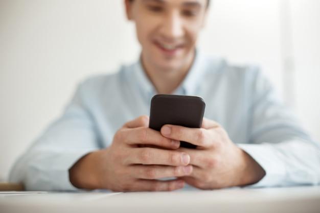 Il mio gadget. neat felice giovane uomo che indossa una camicia bianca e sorridente e in possesso di un moderno telefono nero sensibile al tocco