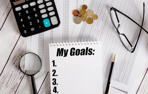 I miei obiettivi scritti in un blocco note bianco vicino a una calcolatrice, contanti, occhiali, una lente d'ingrandimento e una penna. concetto di affari