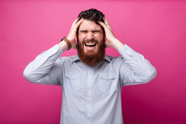 Mi fa male la testa! sono stressato. uomo che soffre di mal di testa su sfondo rosa.