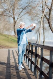 Il mio hobby. gioiosa vecchia donna che scatta foto mentre si cammina nel parco