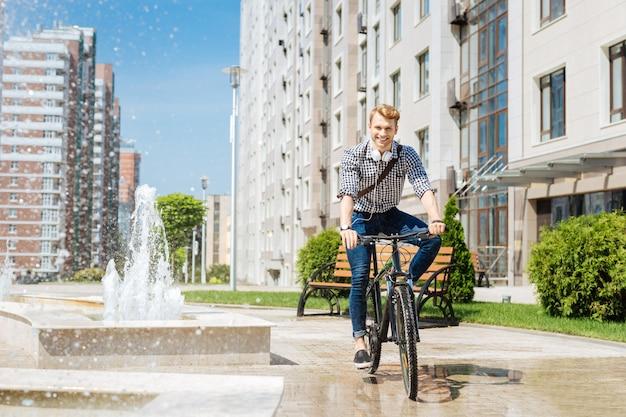 Il mio hobby. gioioso uomo positivo in sella a una bicicletta mentre si gode i suoi fine settimana